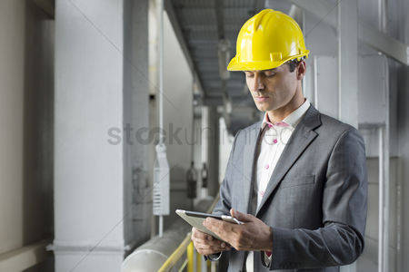 Supervisor : Young male architect using tablet computer in industry