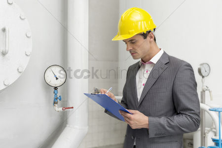 Supervisor : Young male supervisor inspecting pipeline in industry
