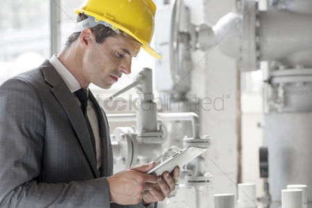 Supervisor : Young male supervisor using tablet pc in industry