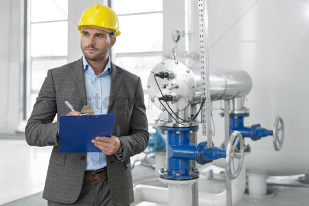 Supervisor : Young male supervisor writing on clipboard in industry
