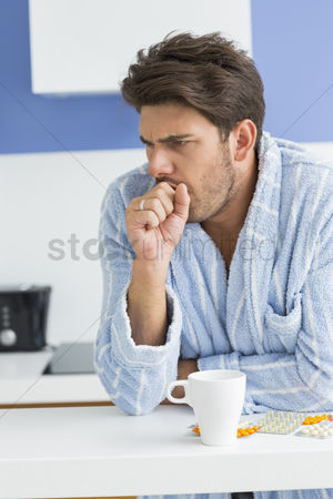 Medication : Young man coughing with coffee mug and medicine on kitchen counter