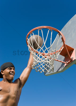 Arm raised : Young man dunking basketball into hoop