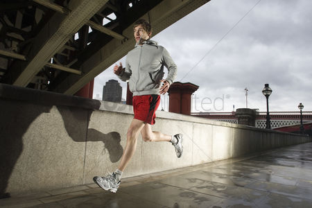 England : Young man jogging besides the thames in london on stormy day