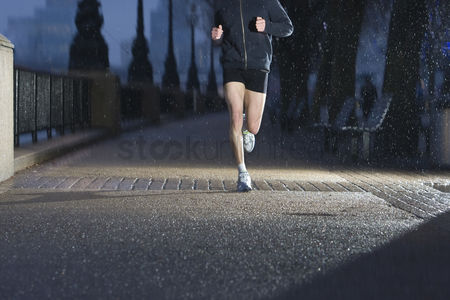 England : Young man jogging on city pavement at dawn in london
