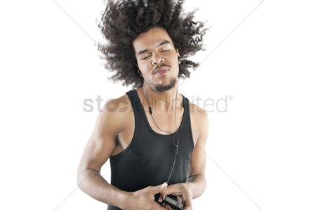 Portability : Young man shaking head while listening to mp3 player over white background