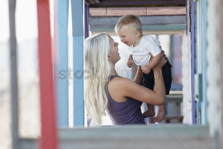 England : Young mother holding son  1-2  on outdoor porch