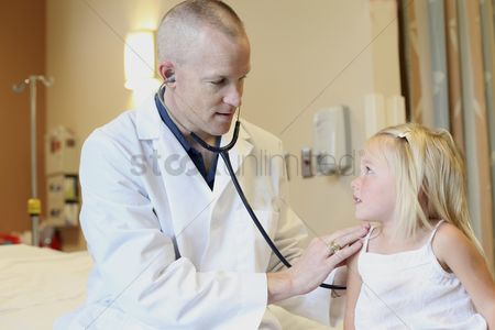 Profession : Young pediatrician listens to young girl s breathing