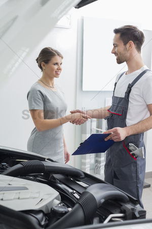 Transportation : Young repair worker shaking hands with customer in car workshop