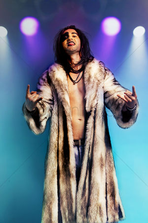 Rage : Young rock musician in fur coat making rebellious hand gestures