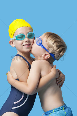 Swimmer : Young siblings in swimwear embracing and kissing over blue background