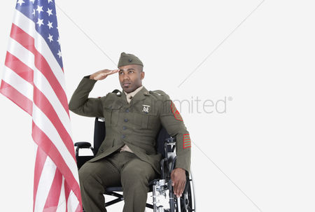 Respect : Young us soldier in wheelchair saluting american flag over gray background