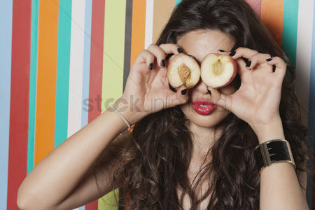 Funny : Young woman covering her eyes with peach against striped background