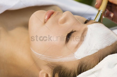 Club : Young woman having facial treatment close-up