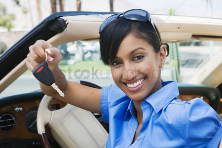 Posed : Young woman holding key to convertible