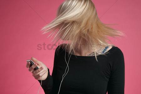 Pink : Young woman holding mp3 player and tossing hair