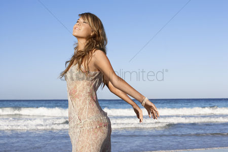 Posing : Young woman in summer dress posing by sea