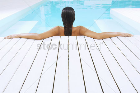Contemplation : Young woman in swimming pool resting on poolside back view