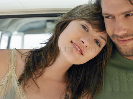 Mid adult man : Young woman leaning on shoulder of young man head and shoulders