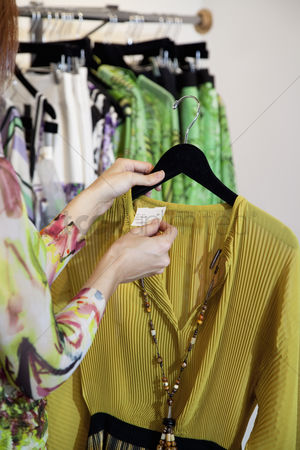 Spending money : Young woman looking at price tag of a dress in clothing store