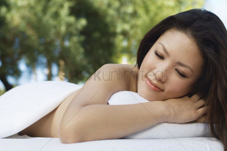 Club : Young woman lying on massage table outdoors