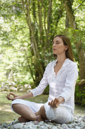 Remote : Young woman meditating by forest river full length