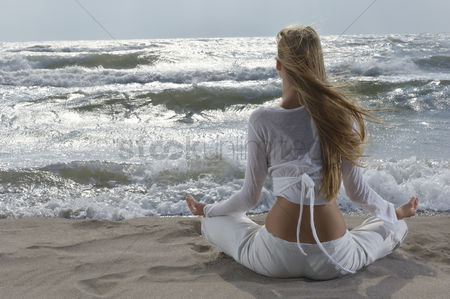 One person : Young woman meditating on beach facing ocean back view