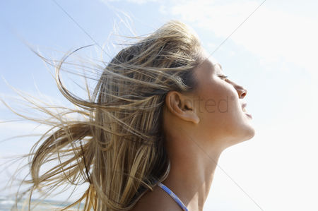 Summer : Young woman on beach with wind-swept hair close up side view head shot