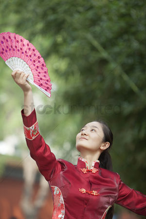 Forbidden : Young woman practicing tai ji with traditional chinese fan