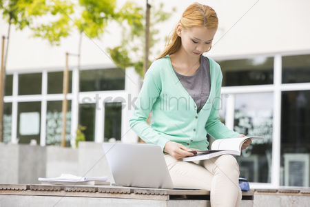 College : Young woman reading book at college campus