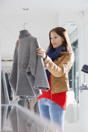 Jacket : Young woman selecting sweater in store