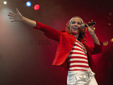Show : Young woman singing on stage in concert low angle view