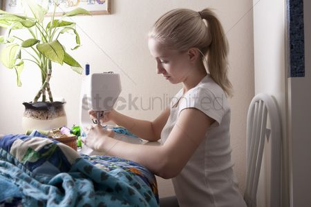 Houseplant : Young woman sits making patchwork at sewing machine