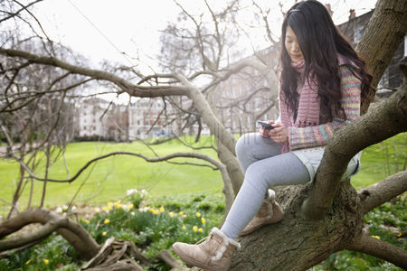 Portability : Young woman sitting on tree branch while text messaging