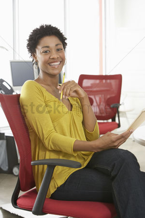 Smiling : Young woman smiling in office portrait