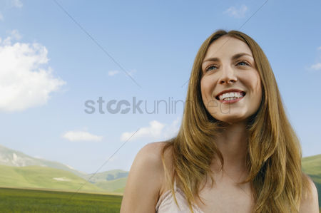 Smiling : Young woman standing in mountain field close up front view