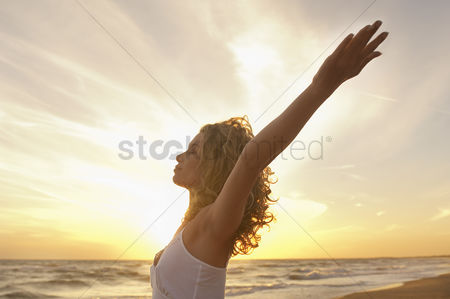 People : Young woman stretching on beach with eyes closed side view