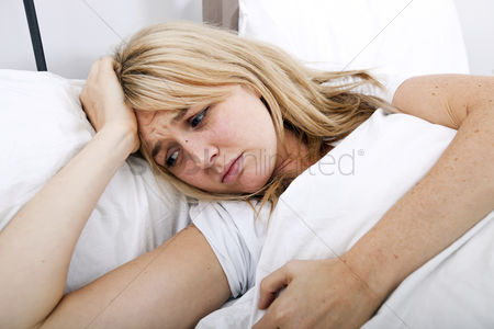 Pain : Young woman suffering from headache in bed