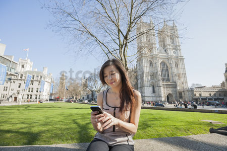 Religion : Young woman using cell phone against westminster abbey in london  england  uk