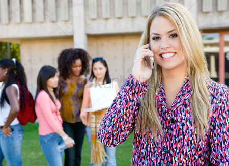 High school : Young woman using mobile phone outdoors