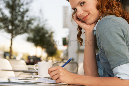 Food  beverage : Young woman writing at outdoor cafe close-up