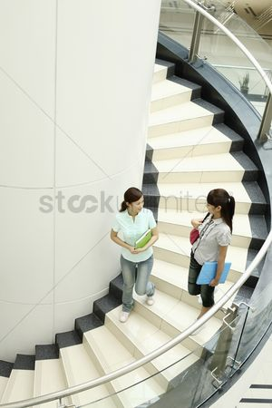 Staircase : Young women chatting while walking down the stairs together